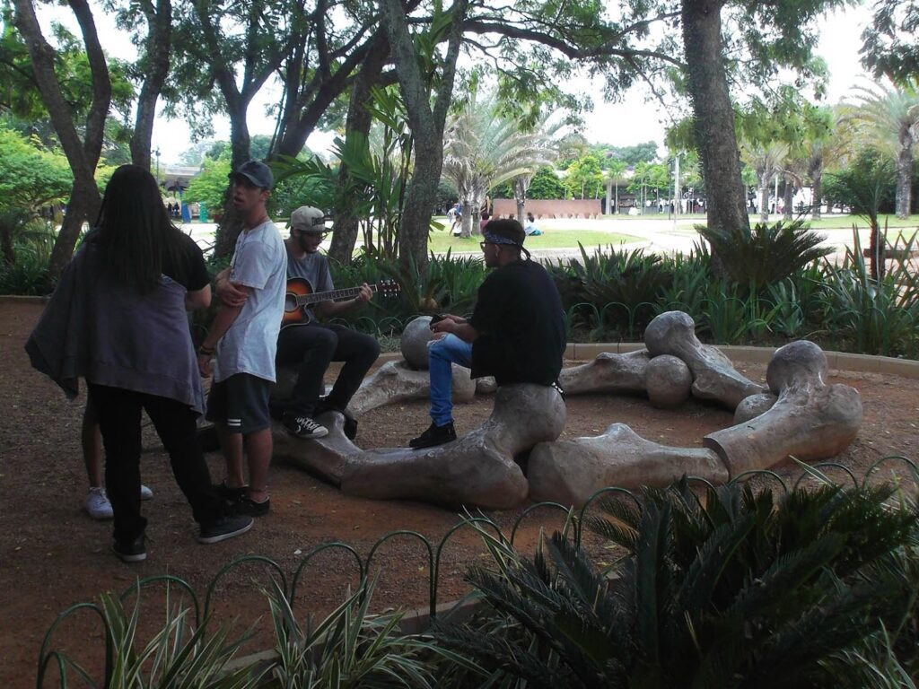 Young people hanging out on Angelo Venosa's sculpture of bones made of aluminium.