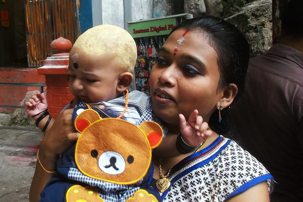 A pious woman with a child at the Batu Caves, mentioned in my guide