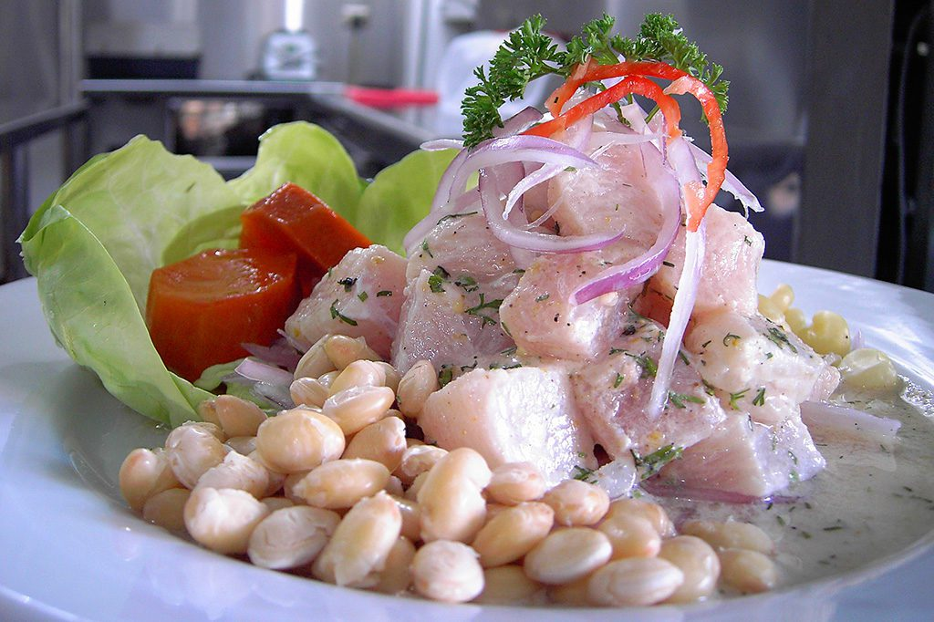 Ceviche accompanied by corn. However, there is an even better version where the corn is roasted - called cancha. (Photo: Picanteria karol, Cebiche de corvina, cropped 2:3, CC BY-SA 4.0 )