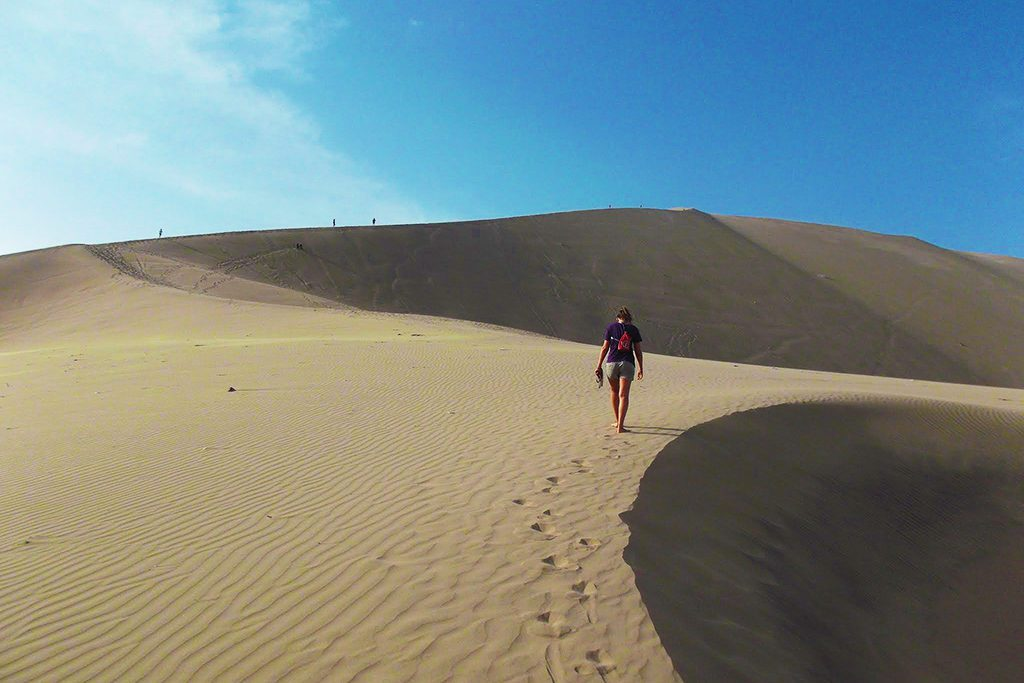 Woman hiking the desert of Huacachina, an oasis close to Ica