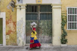 Woman in traditional clothing walking on a street in Cartagena
