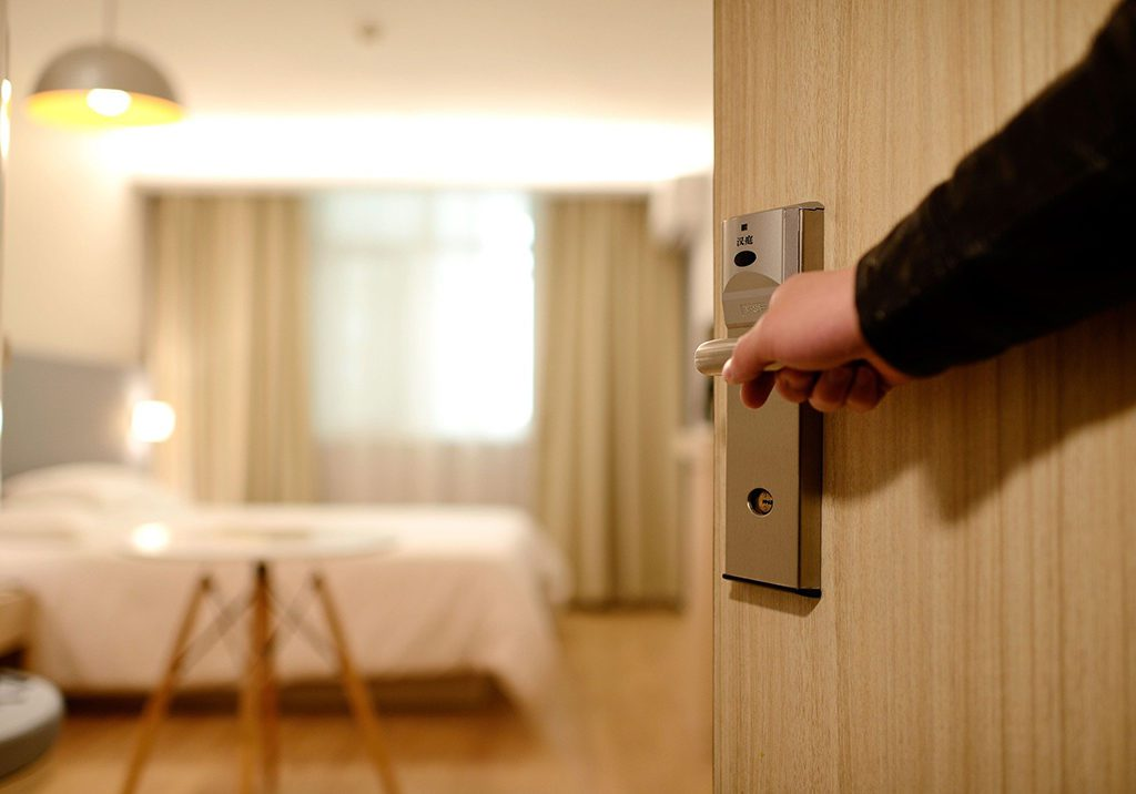 A man opening the door to a hotel room that was booked ahead or the guest just walked in.