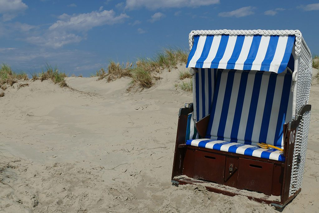 Hooded wicker chairs on the beach of Borkum West of East Frisia