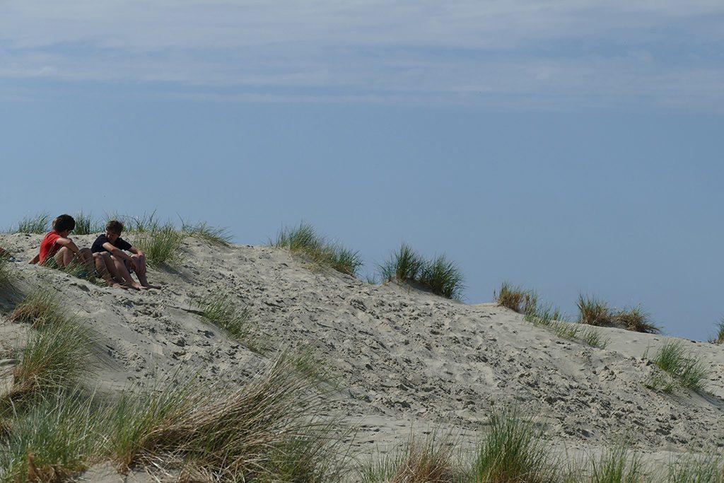 Boys sitting on the Dunes of Borkum West of East Frisia