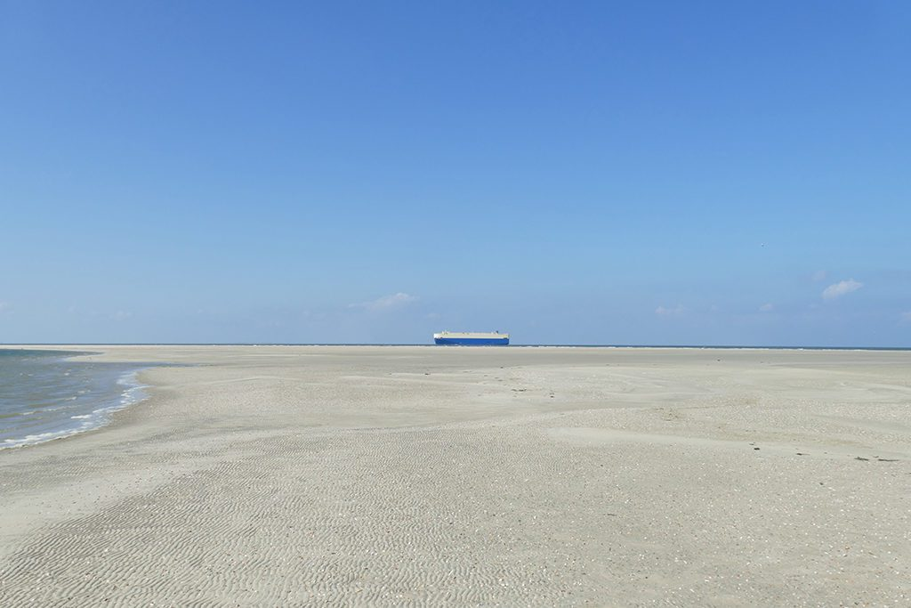 Beach of Borkum with a Tanker in the background