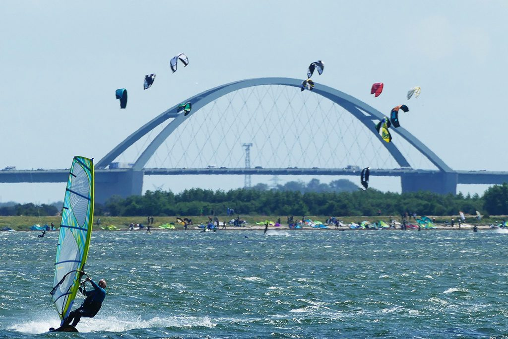 Kites'n'Surfers in all colors in front of the iconic Fehmarnsundbrücke.