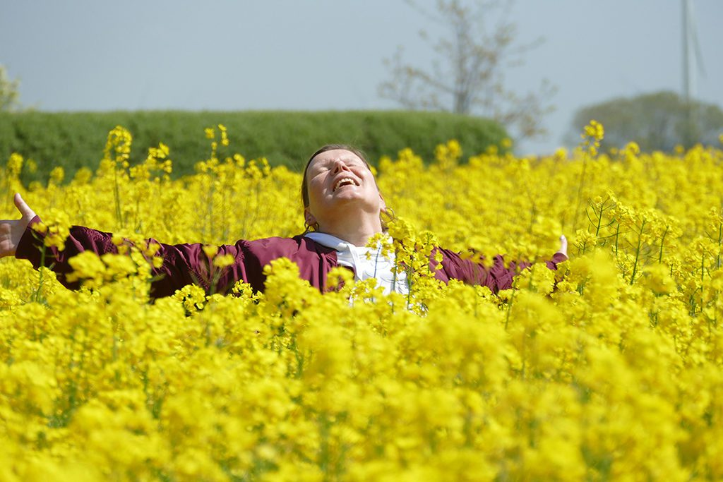 Renata Green in a field of Colza on the Island of Fehmarn in Germany