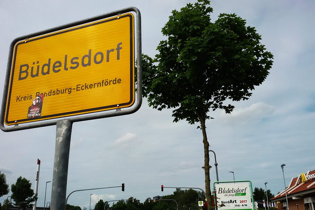 City sign Büdelsorf and a sign advertising for the NordArt2017