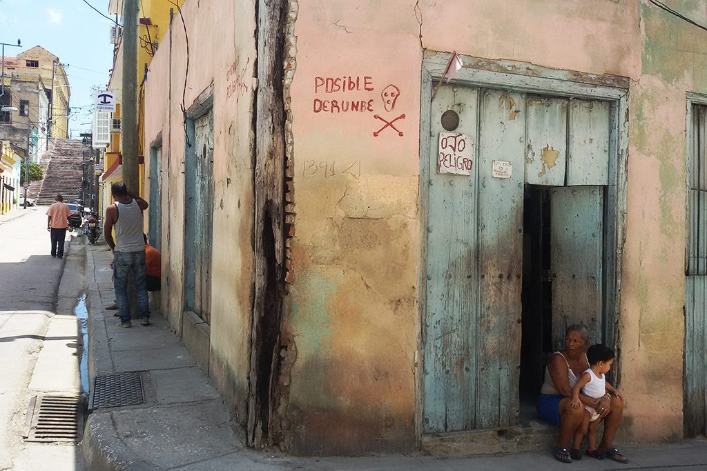 A lady and a little boy at the doorstep of a deteriorating building in Santiago de Cuba