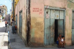 Woman with a little boy sitting in front of a house with a warning sign in Santiago de Cuba.