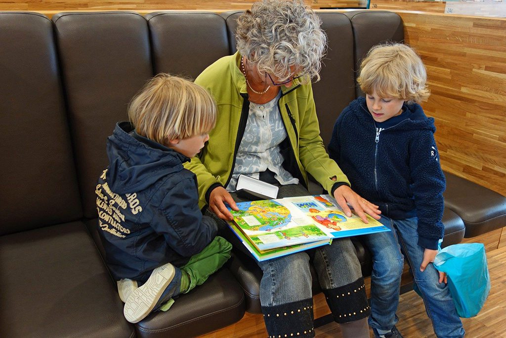 Lady showing a book to two boys
