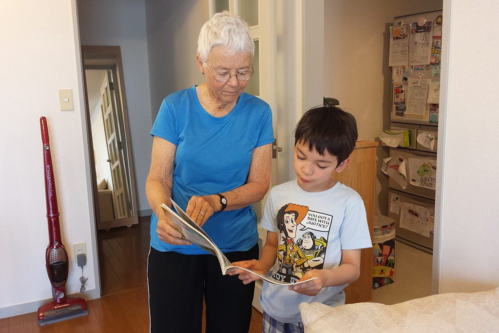 Lady showing a book to two boys  illustrating the post on how to become an au pair