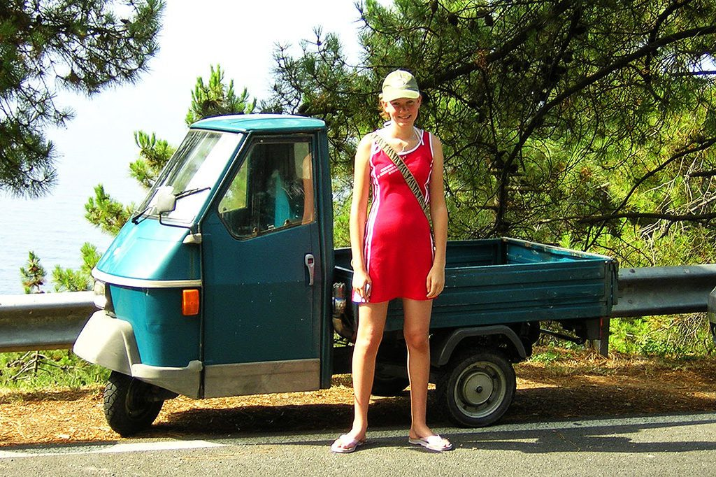 Young girl standing next to a small car at the CINQUE TERRE - The World's Most Picturesque Hiking Trails