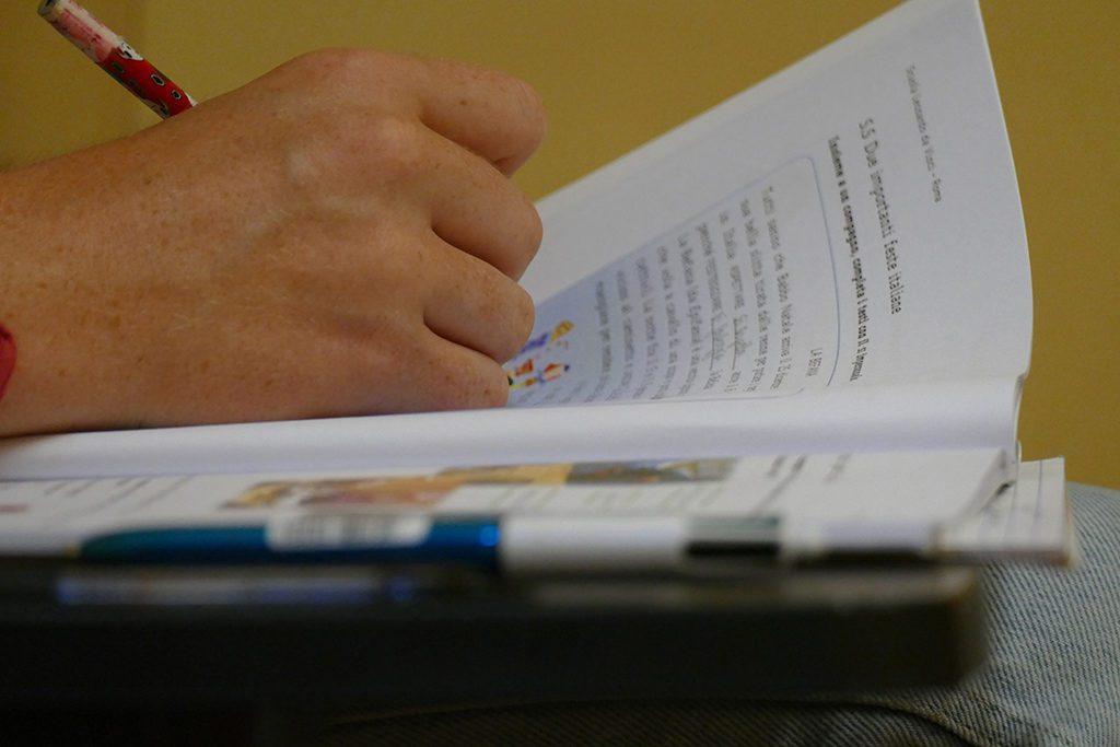Student at the Scuola Leonardo da Vinci writing Italian in an exercise book