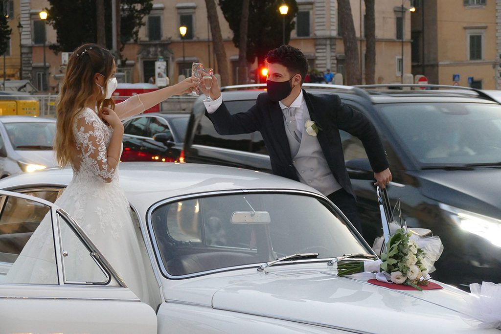 Married couple clinking glasses on the Piazza Venezia, wearing masks
