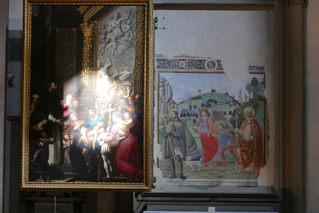 Jacopo Ligozzi's painting St. Raymond Resuscitating a Child sheltering Francesco Botticini's fresco showing the Arcangel Raffael accompanied by Tobias between Saint Rocco and Saint Augustine.