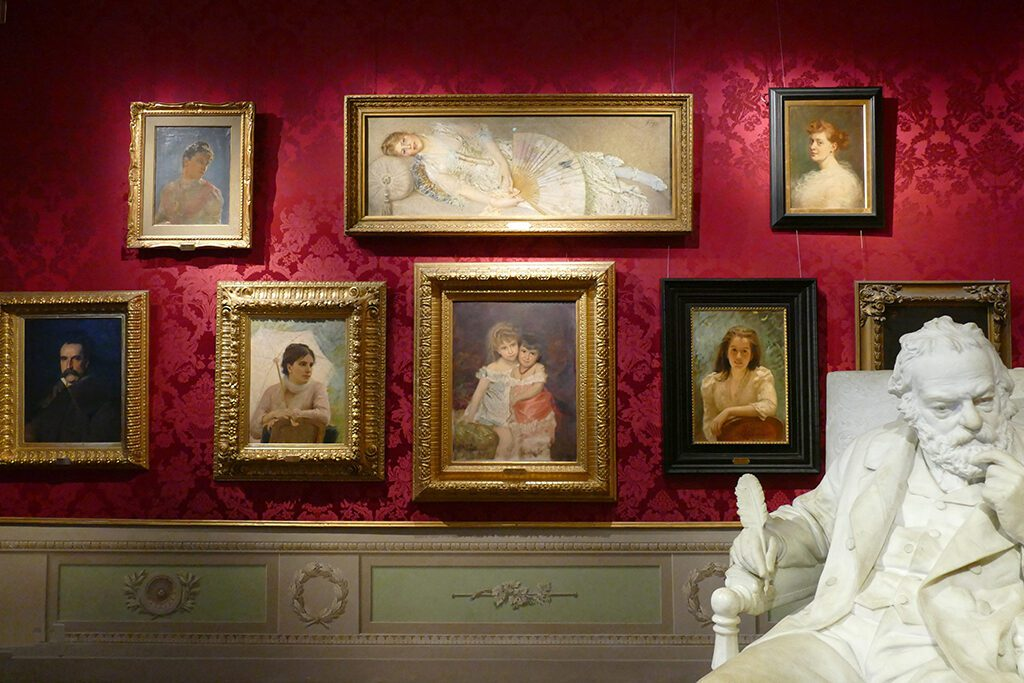 Paintings from the 19th century behind Gaetano Trentanove's sculpture of Victor Hugo at the Palazzo Pitti