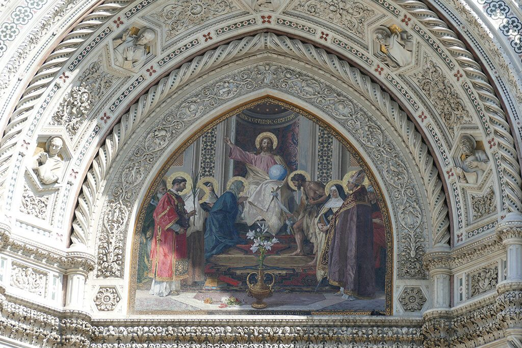 Christ enthroned with Mary and John the Baptist, a Mosaic by Nicolò Barabino above the Cathedral's central portal door.