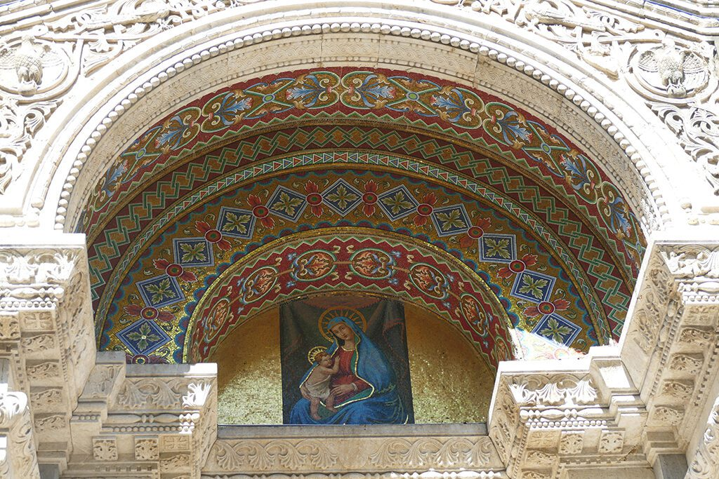The central portal, artistically carved from wood. It shelters the richly decorated mosaic of Our Lady of the Snow in La Spezia.