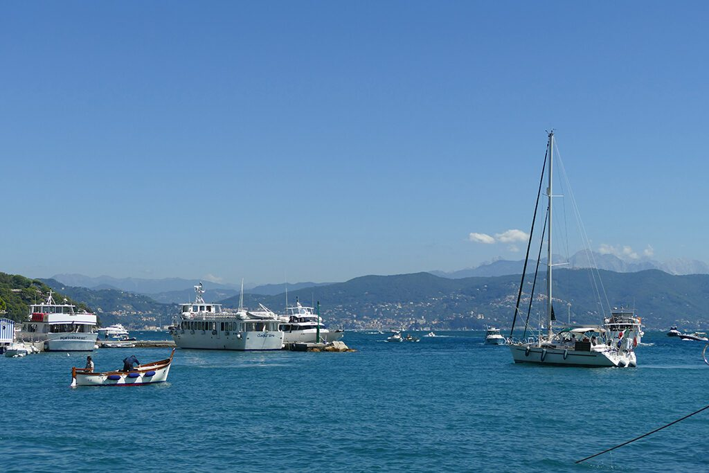 View of a small fishing boat, some ferries, and a posh yacht in the harbor of La Spezia.