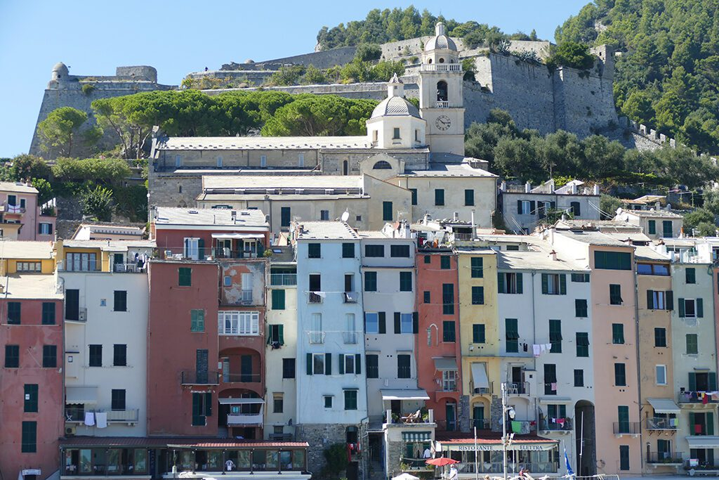 The colorful houses of Porto Venere in the first row, the Romanesque church of San Lorenzo behind, and the Castello Doria in the backdrop.