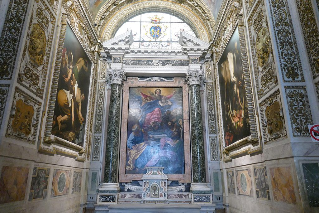 The Assumption of the Virgin by Annibale Carracci flanked by  Caravaggio's paintings Conversion of Saint Paul and Crucifixion of Saint Peter at the  Basilica Parrocchiale Santa Maria del Popolo