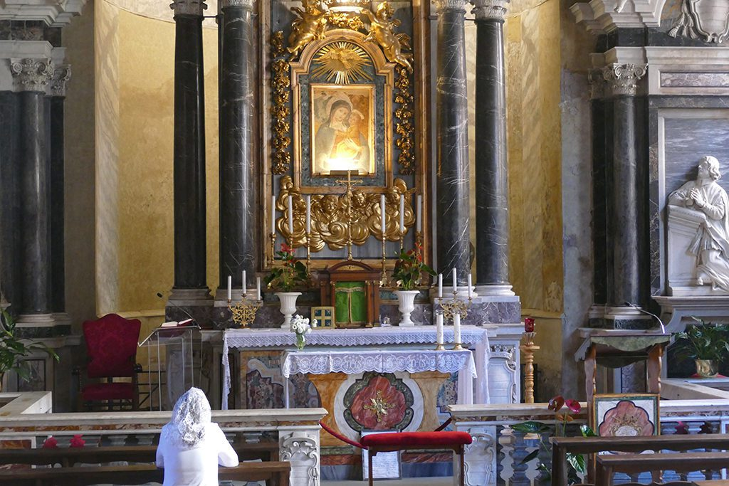 Lady praying at a church in Rome