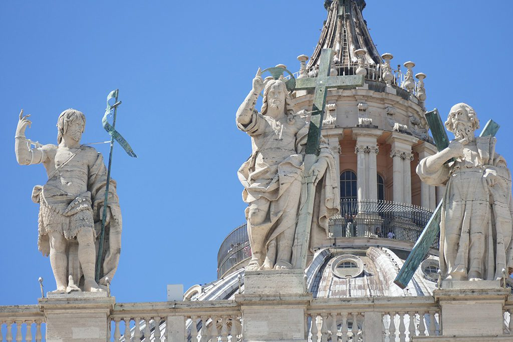 Statues of Jesus Christ, John the Baptist, and Apostle Andrew on the facade of Saint Peter's Basilica.