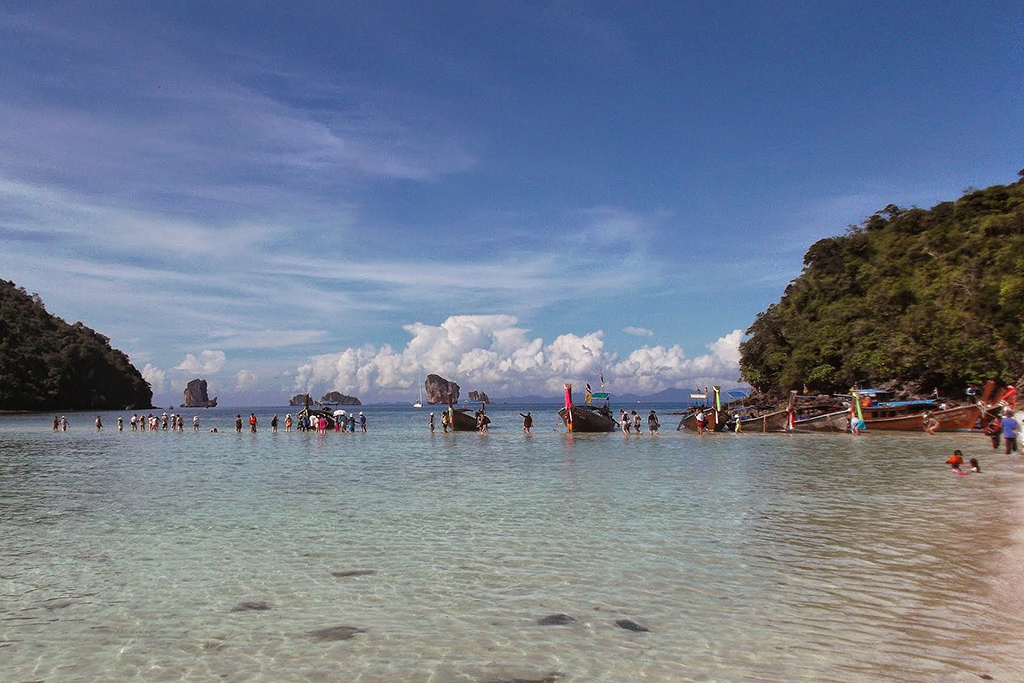 Tourists wading through the Andaman Sea, one of the must-see places in Thailand