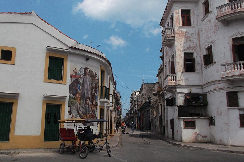 Bicitaxis waiting in front a mural on calle San Ignacio in Havana