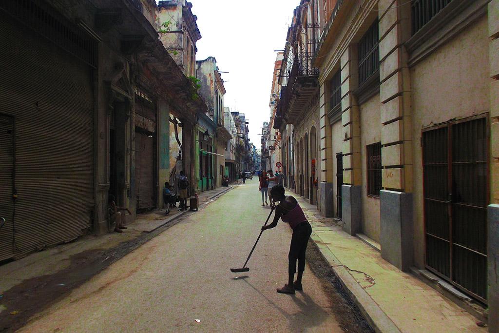 Woman cleaning street in Havana