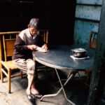 Old gentleman writing in Hoi An