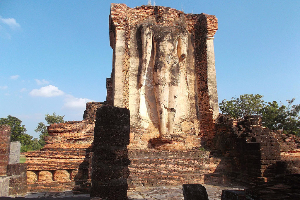 Headless Buddha statue stands on its weathered structure and ruins at Wat Chetuphon