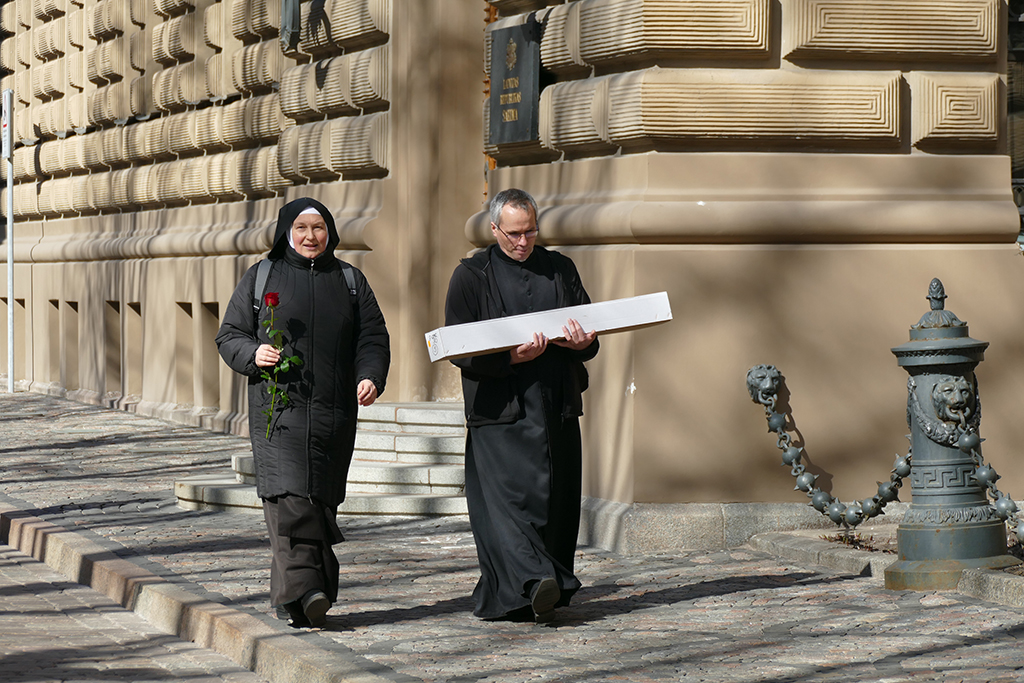 Riga A nun and a priest in front of St. Jacob's Church