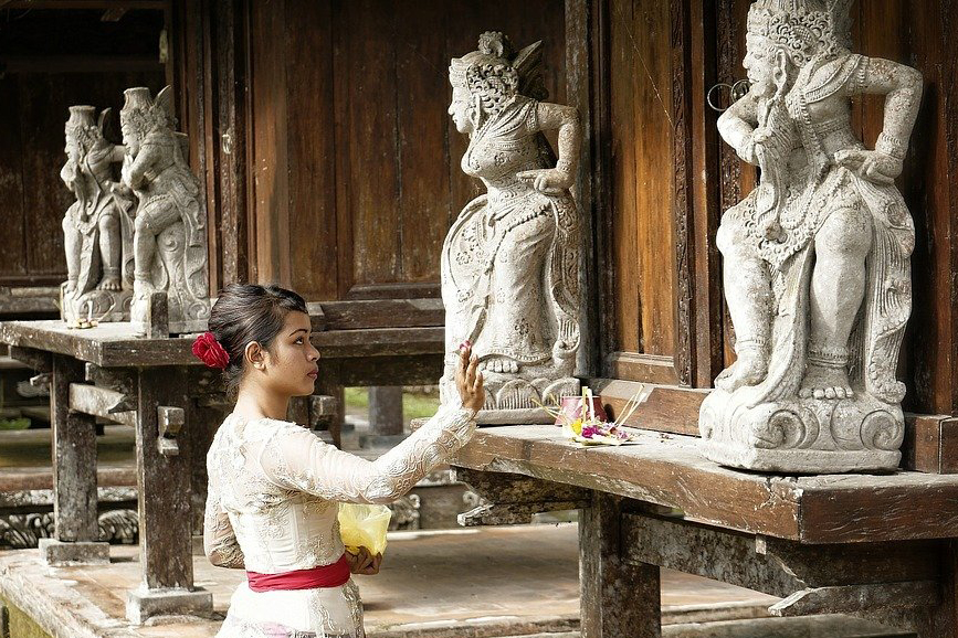 Lady placing an offering bowl at a temple.