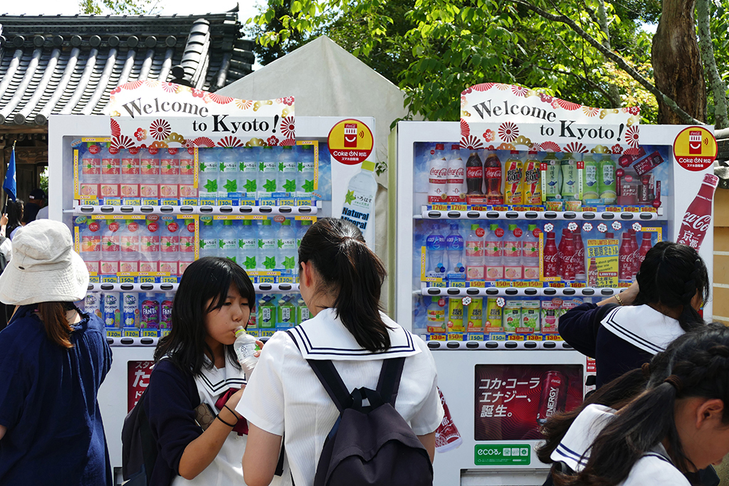 Students buying drinks from vending machines in Japan