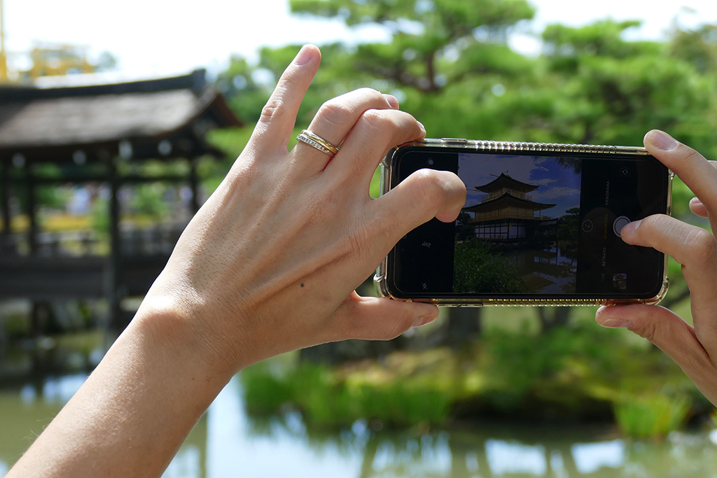 Lady taking a picture of the Golden Pavilion Kinkakuji at Kyoto