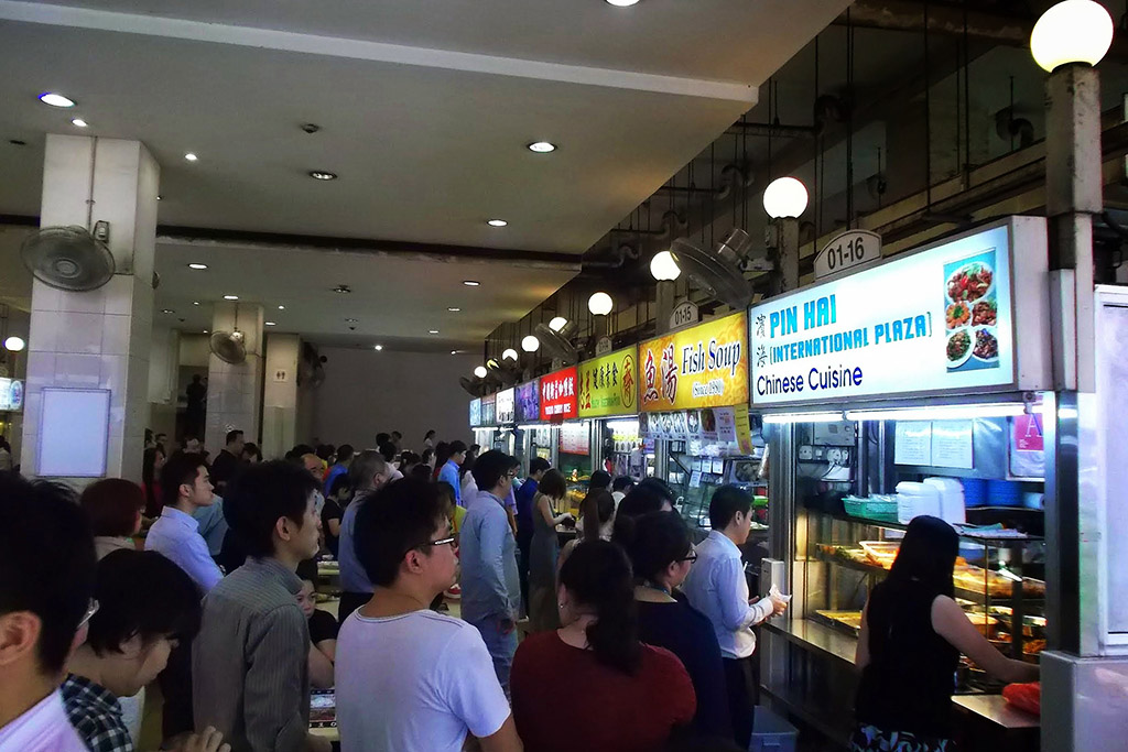 People standing in line at a food court in Singapore