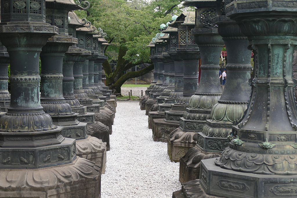 The long way to the Toshogu Shrine lined with old stone lanterns at the Ueno neighborhood in Tokyo