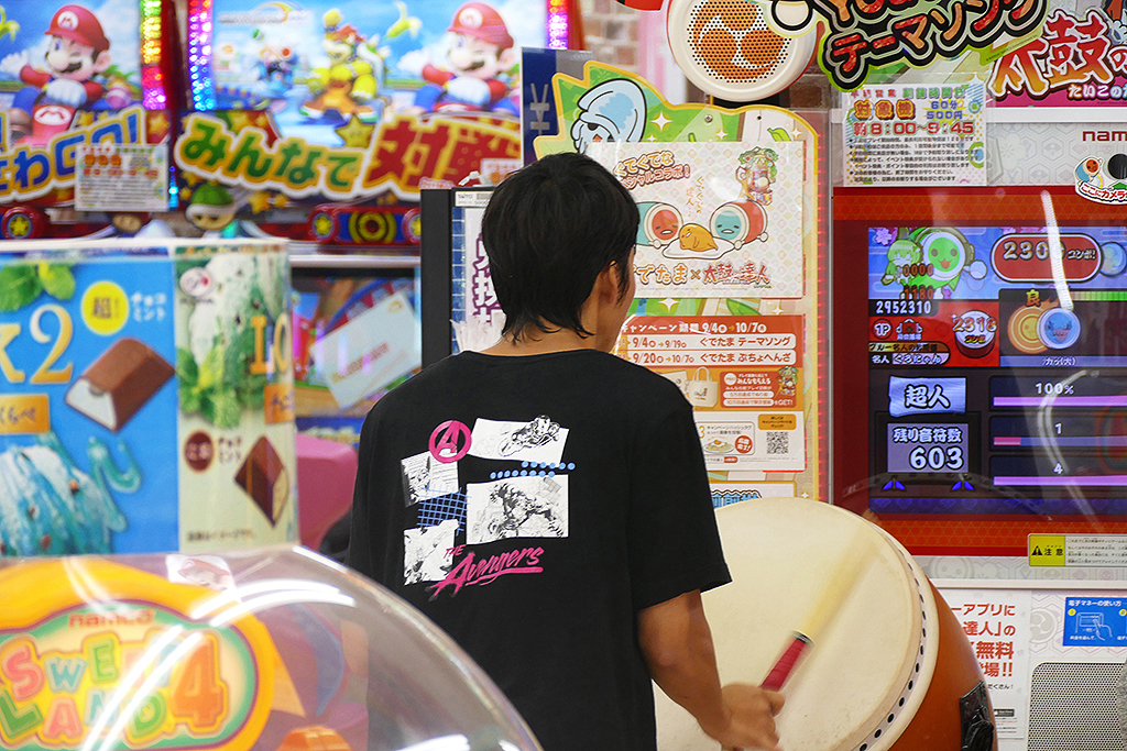 On the Osaka station's lower level: A young man drumming his heart out at the Taito Arcade.