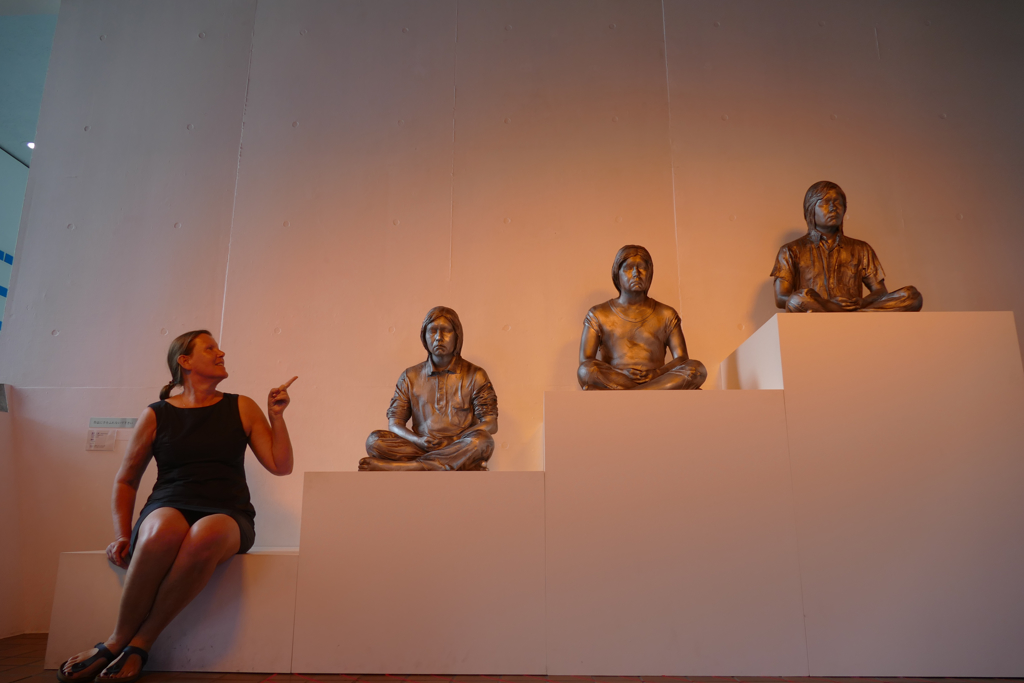 Posing with three statues at the Hakone Open Air Museum