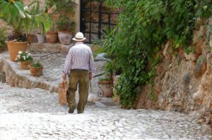 Old man walking down a cobble street in Fornalutx on the island of Mallorca