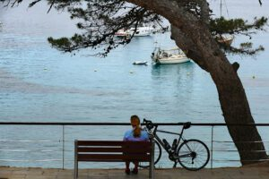 Woman resting on a bench at Sant Elm