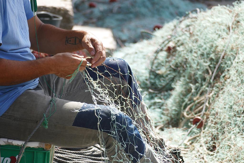 Fisherman fixing a net at Cala Figuera on Mallorca's East Coast.