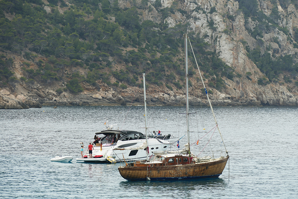 All kinds of vessels are bobbing off Sant Elm's shore.