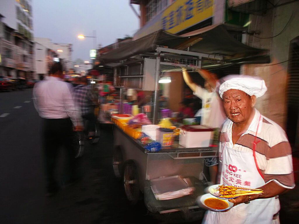 This gentleman is serving Satay skewers, one of the most iconic Malaysian specialties.