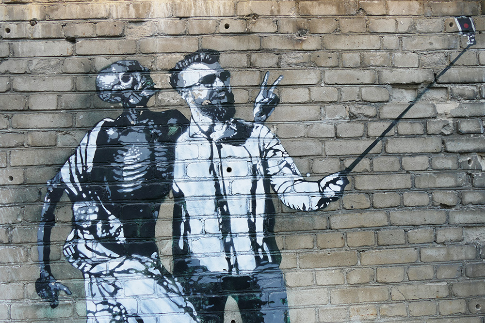 Mural of a man taking a selfie with death