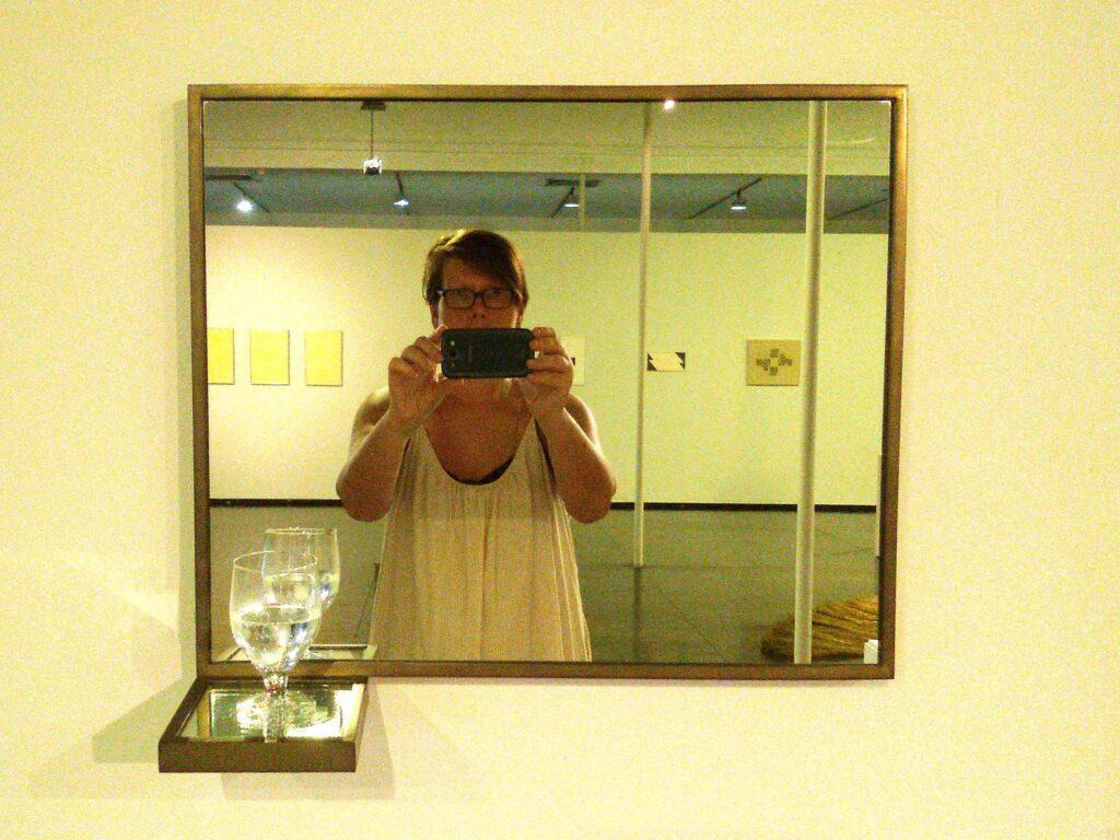 Reflection of Renata Green in Waltercio Caldas' installation Água/Cálice/Espelhos at the MAM