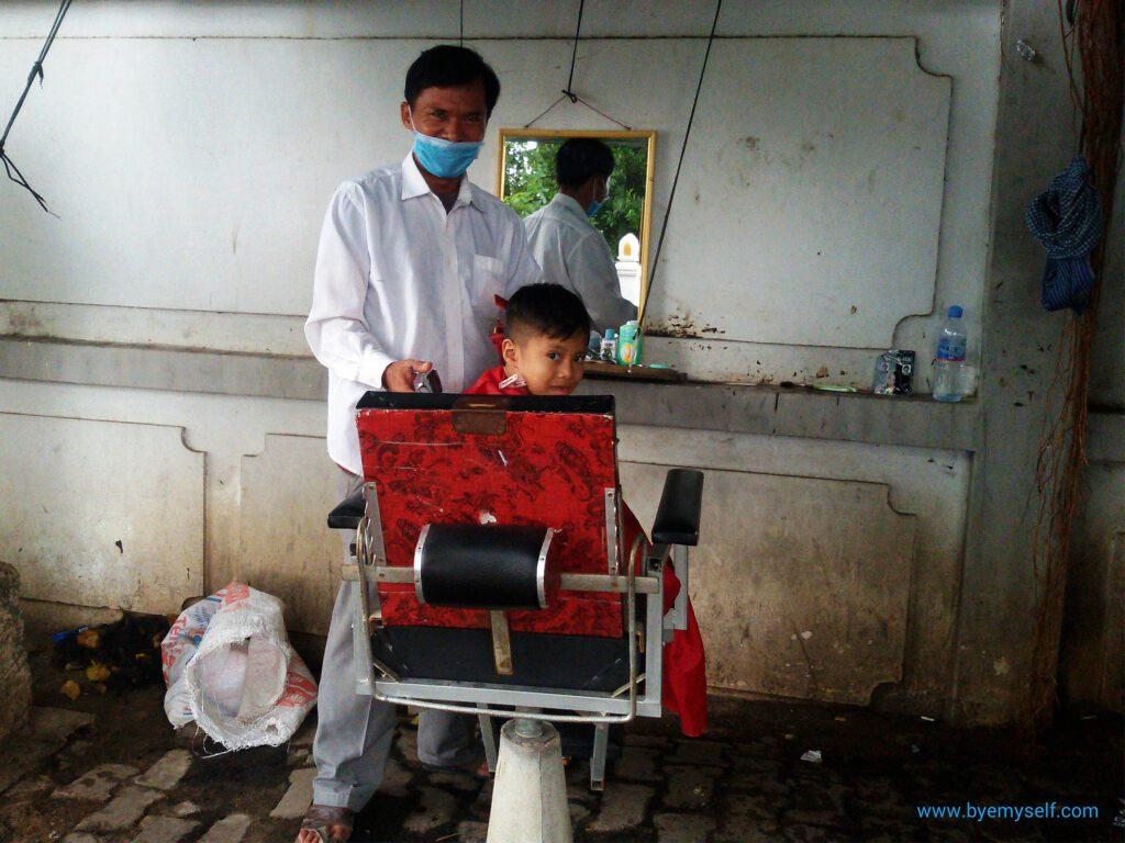 Boy getting a haircut in Phnom Penh, Cambodia