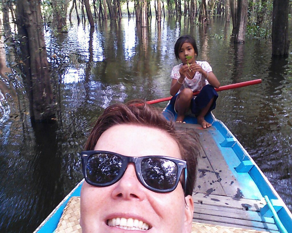 Little girl rowing a tourist through a water wood
